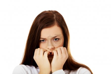 Photo for Young stressed woman biting her nails. - Royalty Free Image