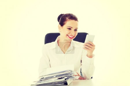 Beautiful business woman sitting by a desk with stack of papers.