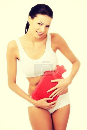 Beautiful slim woman holding hot water bottle.