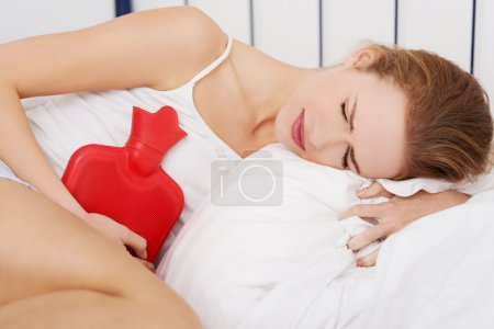 Close up of woman  with hot water bottle in bed