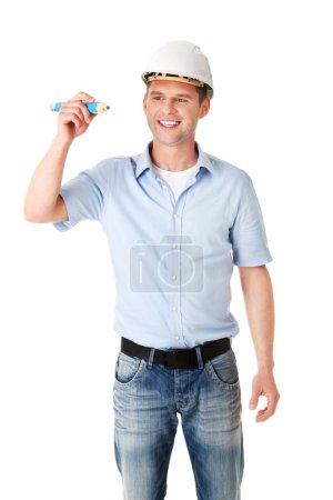 Photo pour Ingénieur en blanc casque écriture sur l'espace de copie avec un énorme crayon - image libre de droit