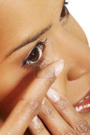 Photo pour Jeune femme mettant une lentille de contact dans son oeil - image libre de droit