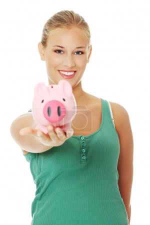 Photo for Young blonde woman holding piggybank - Royalty Free Image