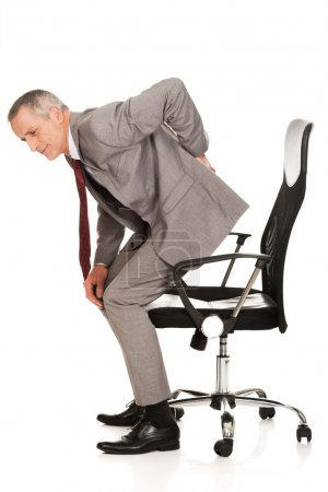 Businessman with backache standing up from a chair