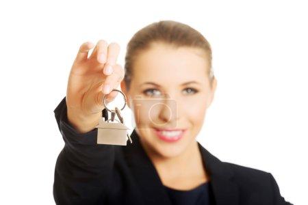 Photo pour Jeune femme d'affaires qui donne les clés de la maison - image libre de droit
