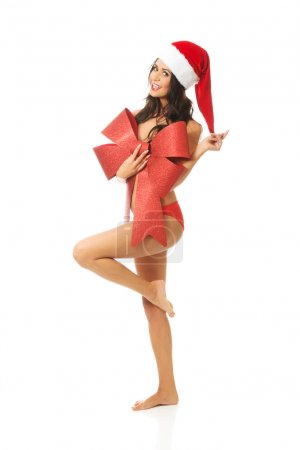 Santa woman standing with bended knee and covering her body by ribbon, looking like a gift