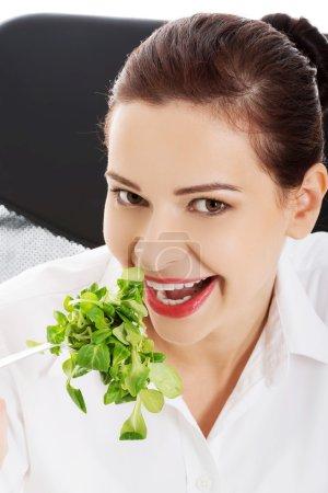 Portrait of a businesswoman eating lettuce
