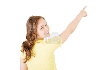 Photo pour Jeune femme de vue arrière pointant vers le haut jusqu'à l'angle - image libre de droit