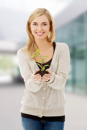 Photo for Woman with plant and soil in hand. - Royalty Free Image
