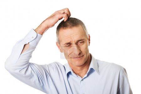 Confused man scratching his head