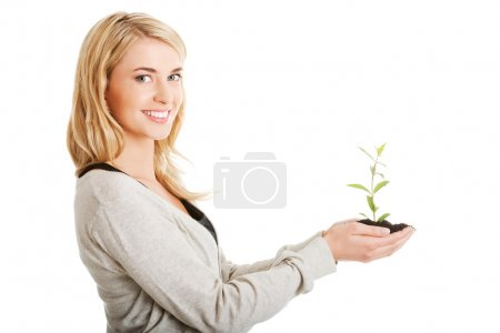 Photo for Happy woman with plant and dirt in hand - Royalty Free Image