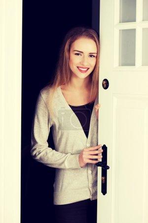 Photo pour Belle femme caucasienne debout près de la porte et de les ouvrir . - image libre de droit