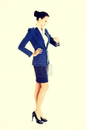 Business woman is looking at her watch on wrist.