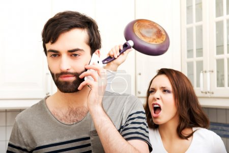 Angry woman hitting man with frying pan.