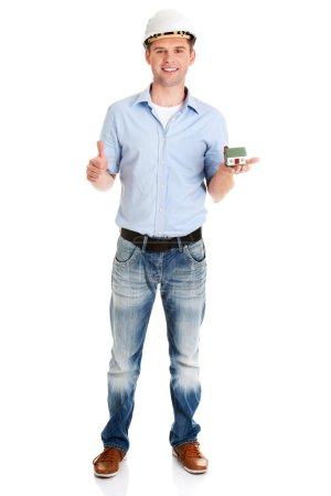 Photo pour Une contremaître tenant une maison modèle en main et faisant un geste OK - image libre de droit