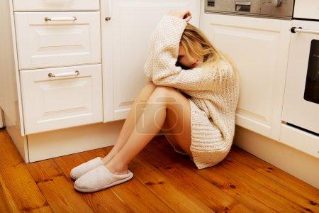 Triste joven solitaria sentada en la cocina .