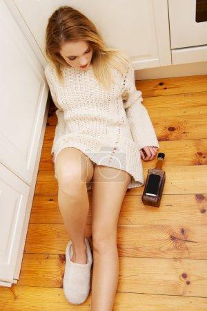Mujer borracha triste sentada en la cocina .