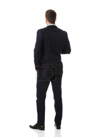 Photo for Handsome businessman standing back to camera. - Royalty Free Image