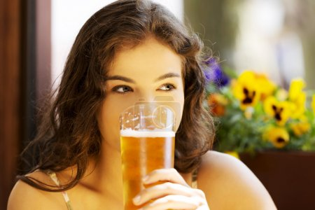 Woman drinking beer in bar
