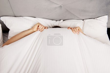 Man hiding in bed under sheets.