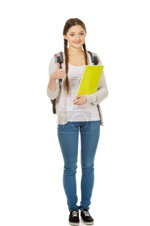 Photo for Teenager girl with school backpack and thumbs up. - Royalty Free Image