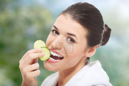 Photo for Woman in bathrobe eating piece of cucumber. - Royalty Free Image