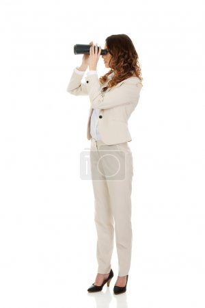 Photo for Caucasian businesswoman looking through binoculars. - Royalty Free Image