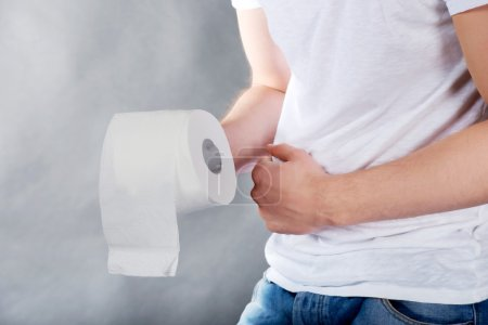 Photo for Young man with stomach issues holding toilet paper. - Royalty Free Image