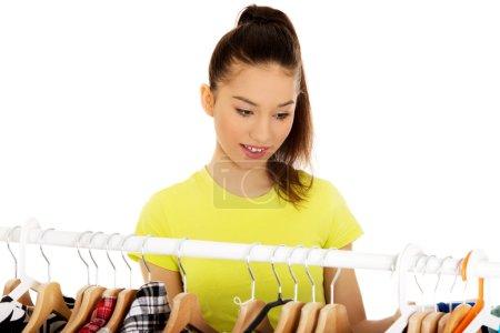 Photo pour Belle jeune femme pensant quoi habiller . - image libre de droit