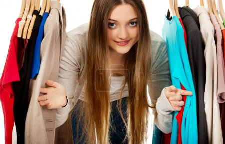 Photo for Happy teen woman between clothes on hanger. - Royalty Free Image