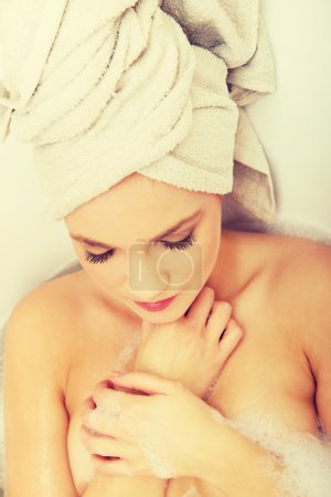 Woman relaxing in bathtub with eyes closed.