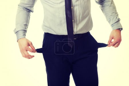 Businessman showing his empty pockets.