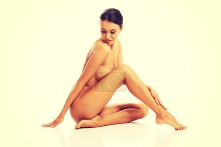 Naked woman sitting and touching her leg