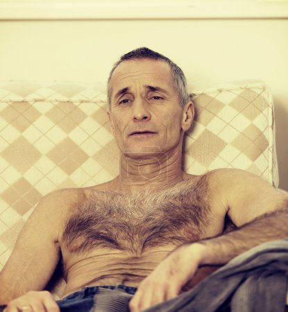 Shirtless man sitting on a sofa
