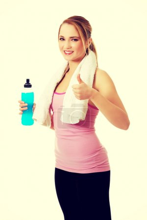 Fitness woman with isotonic drink and ok sign.