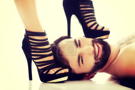 Sexy woman's foot in high heel on man's face, domi...