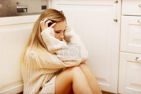 Triste mujer solitaria sentada en la cocina .