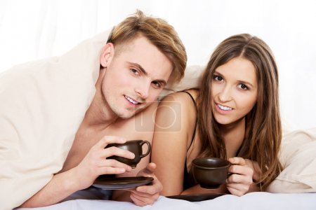 Happy couple drinking coffee in bed.
