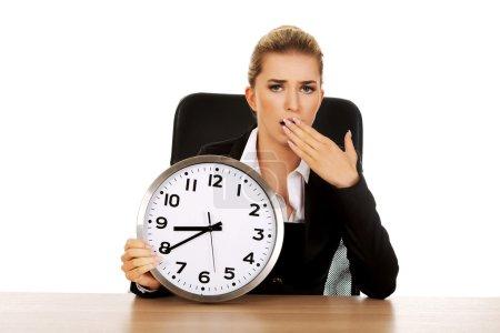 Femme d'affaires béant avec une horloge
