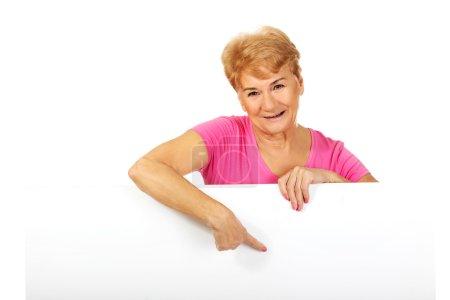 Photo pour Femme âgée souriante pointant vers quelque chose sur une bannière vide . - image libre de droit