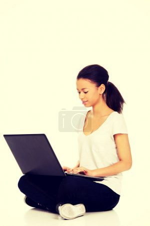 Woman sitting with laptop.