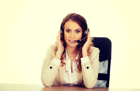 Shocked call center woman by a desk.