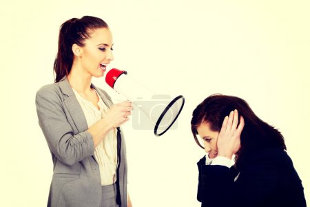 Photo for Businesswoman screaming with megaphone on her friend. - Royalty Free Image