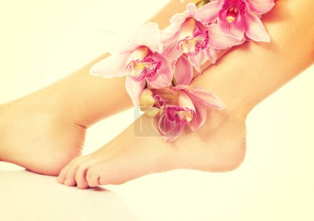 Woman legs with pink flowers.