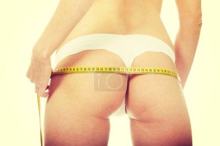 Slim woman measuring her butt.