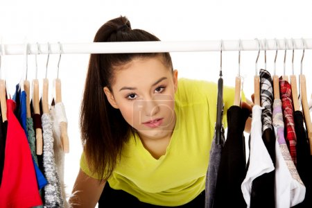 Photo pour Jeune belle femme avec des vêtements sur cintre . - image libre de droit