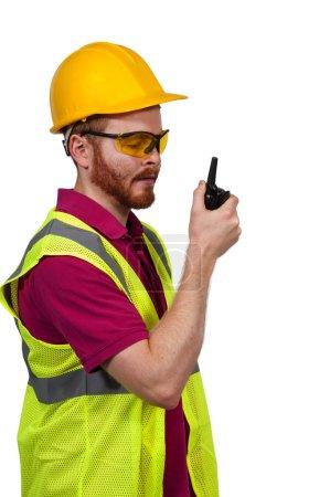 Photo pour Bel homme travailleur de la construction parlant sur un talkie-walkie - image libre de droit