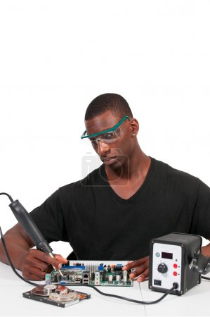 Photo for Man repairing a printed circuit board with a forced air soldering iron - Royalty Free Image
