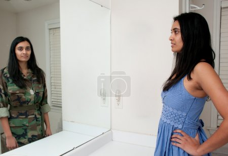 Photo for Woman looking in a mirror seeing herself as a soldier - Royalty Free Image