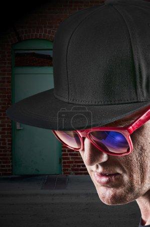 Photo pour Beau homme portant une casquette de baseball en coton élégant et des lunettes de soleil - image libre de droit